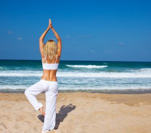 Healthy yoga exercise on the beach, slim sporty body training, leisure & meditation, vacation, sport, health care concept, over natural background