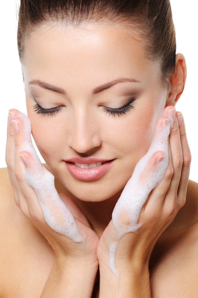 woman washing her face - Healthy Summer Skin